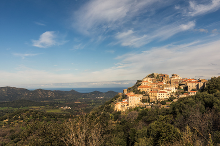 The Balagne village of Belgodere in the sunshine above the Regino valley with the Mediterranean and blue skies behind