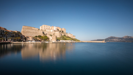 Slow shutter image of the citadel and harbour entrance at Calvi in the Balagne region of Corsica with clear blue sky and smooth calm waters