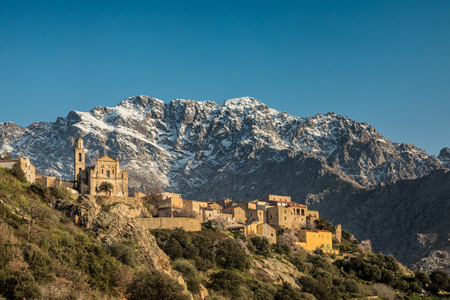 Mountain village of Montemaggiore in the Balagne region of Corsica with a snow capped Monte Grosso mountain behind and clear blue sky Stock Photo