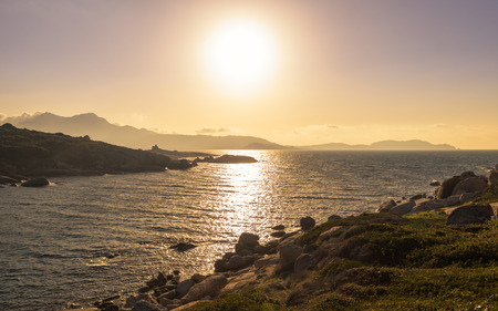 Sun setting over Calvi bay in Corsica with a silhouetted ruin of a Genoese tower with the citadel of Calvi and Revellata in the distance