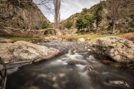 Mountain stream cascading between rocks and under an ancient stone Genoese bridge near Mausoleo in the Balagne region of Corsica Stock Photo