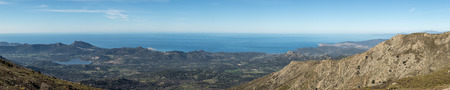 lac: Panoramic view looking over the lush green Regino valley towards LIle Rousse and the coastline of the Balagne region of Corsica with blue sky and blue Mediterranean in the distance Stock Photo