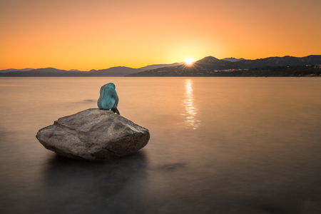 Bronze mermaid sculpture called Sirenella di LIsula Rossa sitting on a rock in the sea at Ile Rousse in the Balagne region of Corsica with the sunrise just appearing over the coast