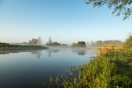river banks: Mist hanging over the River Nene and surrounding fields at Woodford Lock in Northamptonshire, England before the sunrise. Stock Photo