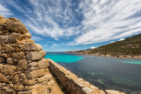 Stone wall of a derelict building next to the translucent Mediterranean sea at Revellata near Calvi in the Balagne region of Corsica under a blue and wispy cloud sky Stock Photo