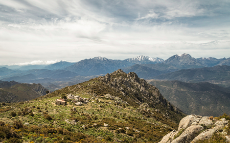 Refuge de Prunincu on the route to Monte Astu near Lama in Corsica with snow capped mountains of Monte Pdru, Monte Cinto and Capu Biancu in the distance