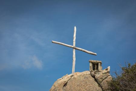 Croix en bois et mémorial de pierre sur un rocher avec un ciel bleu à l'extérieur du refuge de Prunincu sur la route du Monte Astu en Corse du Nord Banque d'images