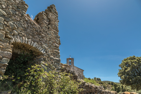 Ancient stone wall of derelict buildings in abandoned village of Casenove near Pietralba in the Balagne region of Corsica with an old chapel with stone bell tower in the background