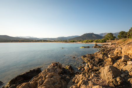 Still and clear Mediteranean water on the rocky coastline at Lozari in the balagne region of Corsica with beach, trees and hills in the distance Stock Photo