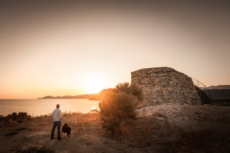 Man & border collie dog looking across Lozari bay as the sunrises behind a Genoese tower on the coast of the Balagne region of Corsica