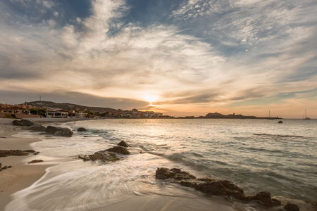 Dramatic sunset over the beach at LIle Rousse in the Balagne region of Corsica with rocks in the foreground, bars and restaurants along the front and the red rock, port and lighthouse in the distance