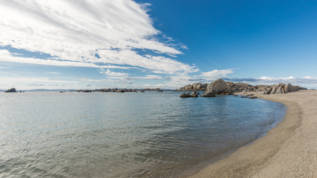 Deserted sandy beach and boulders on coast of Cavallo island near Corsica in France with blue Mediterranenan and blue skies with wispy clouds above