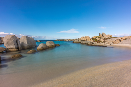 Deserted sandy beach and boulders on coast of Cavallo island near Corsica in France with blue Mediterranenan and blue sky Stock Photo