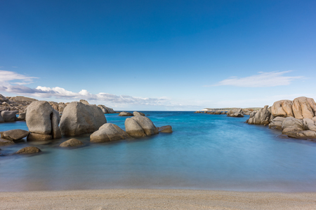 Slow shutter image of deserted sandy beach and boulders on coast of Cavallo island near Corsica in France with blue Mediterranenan and blue skies with wispy clouds above