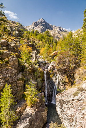 Waterfall cascading over rocks into a clear, shallow pool and between pine trees with Paglia Orba mountain in distance near the GR20 trail in Corsica