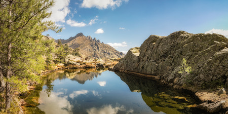 Panoramic view of small lake at Paglia Orba surrounded by rocks, pine trees and mountains near the GR20 hiking trail in central Corsica