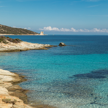 Ruins of the Genoese tower at Mortella with a turquoise mediterranean sea and rocky coastline of the Desert des Agriates near St Florent in Corsica