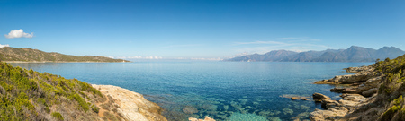 Panoramic view of calm and clear Mediterranean sea on the coast of the Desert des Agriates near St Florent in Corsica with the Genoese Mortella tower and Cap Corse in distance Stock Photo