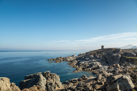 Rocky coastline and transparent turquoise Mediterranean sea below the Genoese tower at Punta Spano on the coast of the Balagne region of Corsica with Cap Corse in the distance Stock Photo