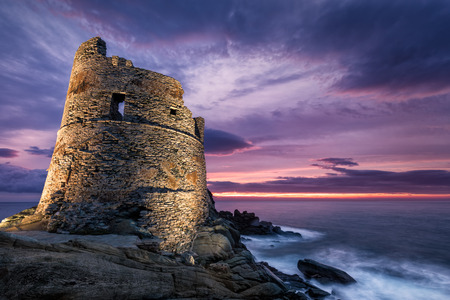 Floodlit Genoese stone tower at Erbalunga on the coast of Cap Corse in Corsica as a dramatic orange and purple sunrise breaks on the horizon