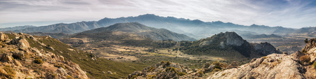 Panoramic view of Monte Grosso and the rugged mountain peaks and valleys of Corsica taken from Capu dOcci near Calvi Stock Photo