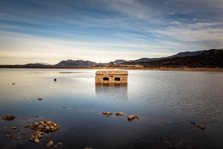 Partially submerged abandoned stone building in Lac de Codole lake in the Balagne region of Corsica with the moon rising behind the distant hills