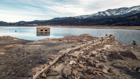 Partially submerged and abandoned stone building in Lac de Codole lake in the Balagne region of Corsica and ancient water channel with snow covered mountains in distance
