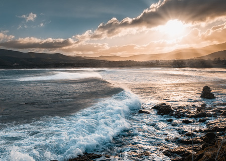 Sun breaking through the clouds onto a turbulent Mediterranean sea at Lozari beach in the Balagne region of Corisca following a winter storm Stock Photo