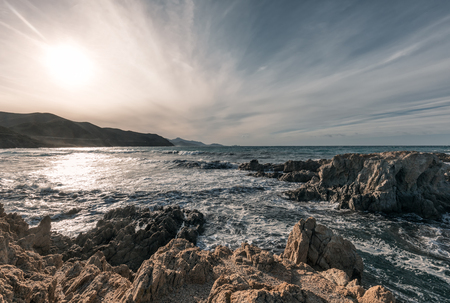 Rough seas and jagged rocks on the coast of the Desert des Agriates at Ostriconi in the Balagne region of Corsica with Ile Rousse in the distance