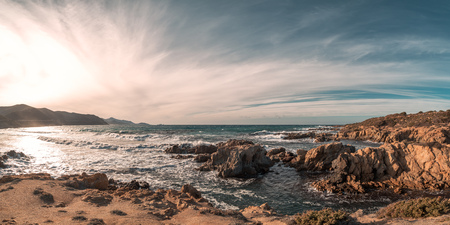 Panoramic view of waves breaking on Ostriconi beach and the coast of the Desert des Agriates in the Balagne region of Corsica with Ile Rousse in the distance Stock Photo