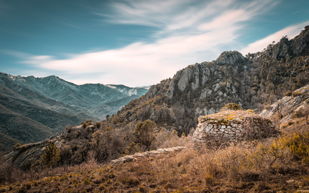 Derelict stone building at an ancient marble mine in the hills above Venaco in central Corsica with snow covered mountains in the distance
