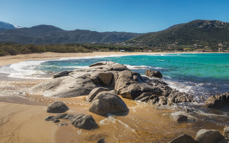Waves washing onto rocks and sand at Algajola beach in the Balagne region of Corsica under a deep blue sky with snow capped mountains in the distance Stock Photo
