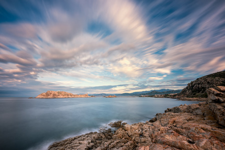 Slow exposure image of evening sun lighting up wispy clouds on the red rock of La Pietra in Ile Rousse in the Balagne region of Corsica 스톡 콘텐츠