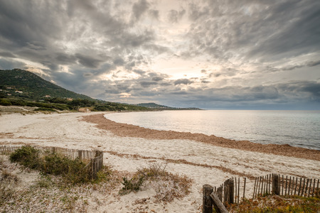 Wispy evening clouds as the sun sets over a deserted Bodri beach in the Balagne region of Corsica