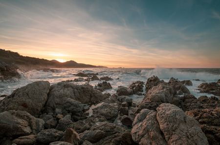 Waves crashing onto rocks at sunset on the coast of the Balagne region of Corsica near Lozari with Ile Rousse in the distance