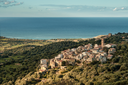 The ancient mountain village of Aregno lit by the afternoon sun and surrounded by autumnal trees in the Balagne region of Corsica with the Mediterranean see in the distance