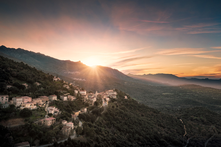 Sun setting behind the mountains over the village of Belgodere in the Balagne region of Corsica