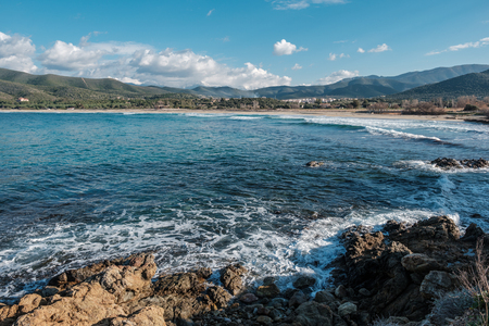 Waves washing onto the rocky coastline at Lozari beach in the Balagne region of Corsica with snow capped mountains in the distance Stock Photo