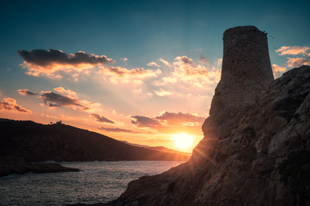 Ancient stone Genoese tower at La Pietra in Ile Rousse in the Balagne region of Corsica silhouetted by a dramatic sun setting over the Mediterranean sea