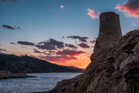 Ancient stone Genoese tower at La Pietra in Ile Rousse in the Balagne region of Corsica with the last rays of the sun setting over the Mediterranean sea
