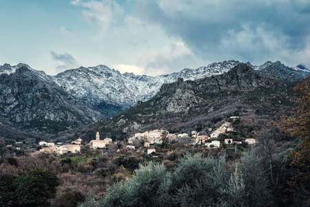 Ancient mountain village of Feliceto in the Balagne region of Corsica with the snow covered mountains and Monte San Parteo in the distance
