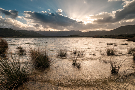 Sun setting behind clouds over Lac de Codole in the Regino valley in the Balagne region of Corsica with snow capped mountains in the distance Stock Photo