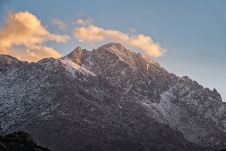 Evening sunlight on the snow capped rocky peak of Monte Grosso mountain the the Balagne region of Corsica Stock Photo