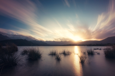 Long exposure image of sun setting behind clouds over Lac de Codole in the Regino valley in the Balagne region of Corsica with reeds in the foreground and snow capped mountains in the distance