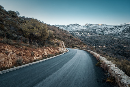 Tarmac road heading towards the village of Speloncato and snow capped mountains of the Balagne region of Corsica