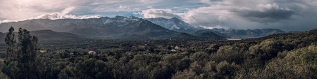 Panoramic view of Regino valley and snow capped mountains in the Balagne region of Corsica with the Codole dam and Monte Grosso and Monte San Parteo in the distance Stock Photo