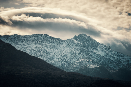 Snow capped mountain peak of Monteo Grosso under cloudy skies in the Balagne region of Corsica