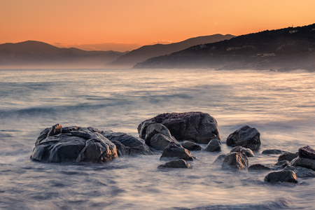 Long exposure image of Mediterranean sea washing over rocks at sunrise near Ile Rousse in Corsica with orange glow over hills in the distance Stock Photo