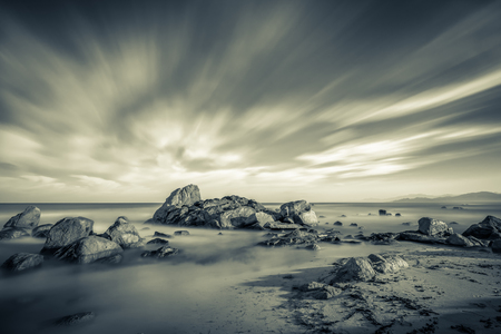 Long exposure black and white image of Mediterranean sea washing over rocks and onto sandy beach at sunrise near Ile Rousse in Corsica with orange glow over hills in the distance