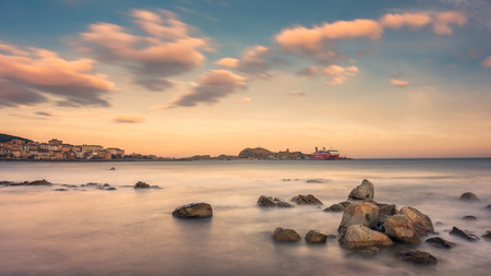 LIle Rousse, Corsica - 5th February 2019. Corsica LInea Ferry waits at sunrise in the port of LIle Rousse in the Balagne region of Corsica. Long exposure image with rocks in the foreground.